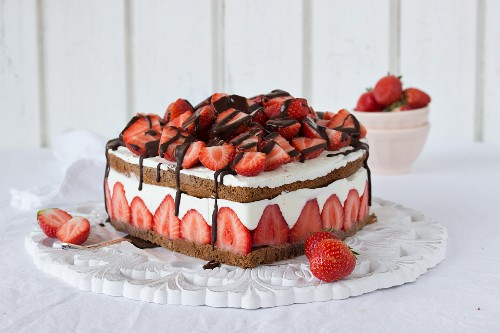 A heart shaped chocolate and strawberry cake with cream