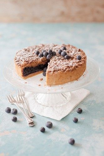 Blueberry crumble cake on a cake stand (vegan)