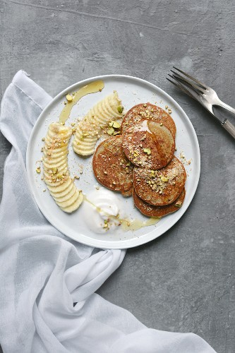 Banana pancakes with coconut yoghurt, pistachios and coconut flakes