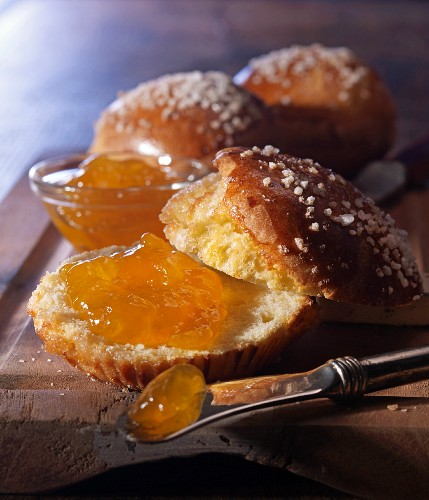 A knife next to a brioche, sliced open, with coarse sugar crystals and apricot jam