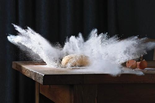 A ball of dough falling onto a floured surface