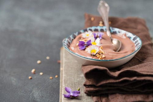 Chocolate pudding with chopped hazelnuts and edible flowers (daisies, violets)
