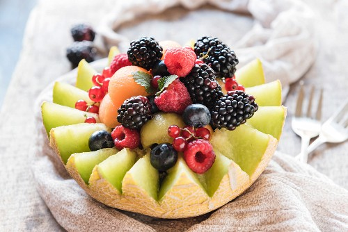 A halved melon filled with melon balls and fresh berries