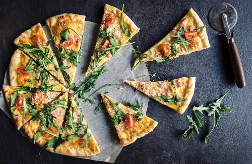 A sliced vegetarian pizza with cheese and rocket