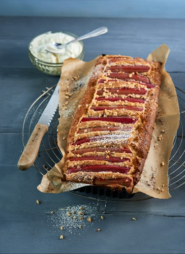 Rhubarb cake with marzipan, wrapped in baking paper, on a cooling rack