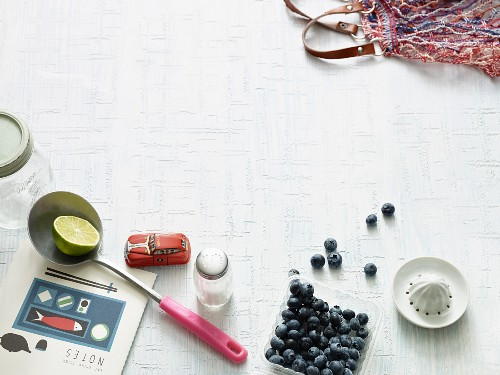 An arrangement of a notebook, a ladle, a salt shaker, blueberries, a lemon squeezer and a shopping bag
