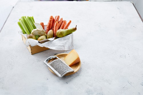 Fresh vegetables (celery, carrots, celeriac) and pears, with cheese and a grater in the foreground