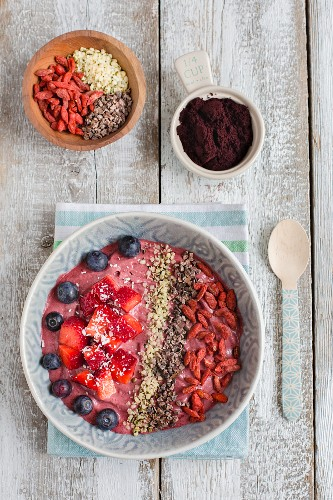 An acai bowl with fresh berries, hemp seeds, cacao nibs and goji berries