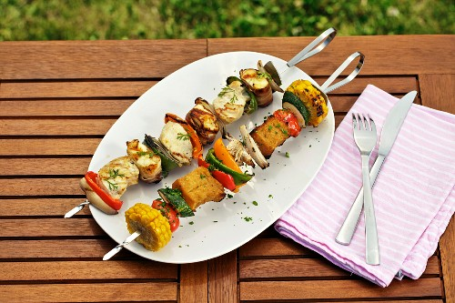 A vegetable skewer with bread chunks, and a chicken skewer with grilled cheese