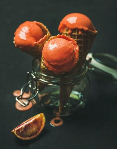 Refreshing summer blood orange ice cream or sorbet scoops in sweet waffle cones in glass jar