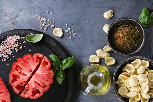 Homemade raw uncooked pasta with whole and sliced organic tomatoes Coeur De Boeuf, salt, seasoning, olive oil and basil