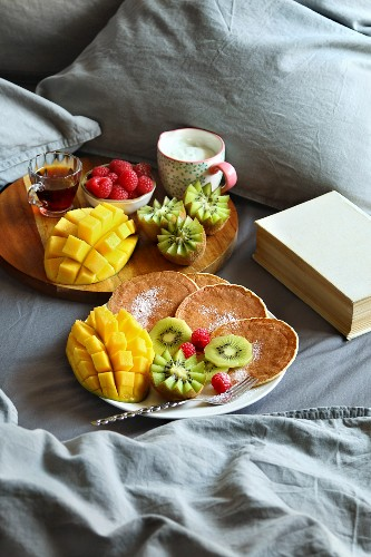 Breakfast served in bed with pancakes, fresh fruit, yogurt and maple syrup