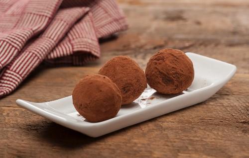 Three chocolate truffles with cocoa powder