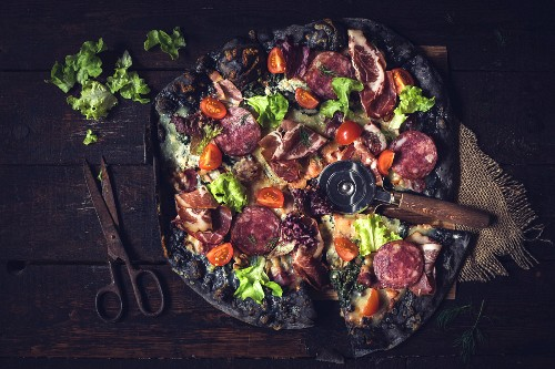 Black pizza with ham, sausage, bacon and vegetables on wooden background