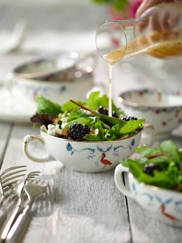 Minz-Brombeer-Salat mit Dressing begiessen