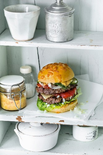 A double burger with beef, maasdam cheese, Joppiesaus mayo, pickled cucumbers, and onions