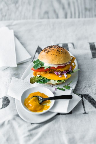 A crispy chicken burger with mango slices and mango ketchup
