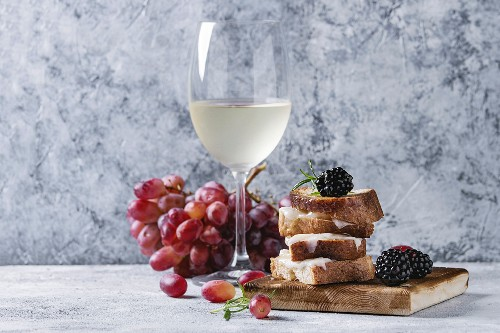 Grilled sandwich with melted goat cheese, blackberry, blueberry, rosemary and honey, served on wooden board with glass of white wine and grape