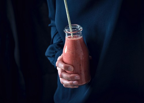 A woman holding a bottle of red smoothie (vegan)