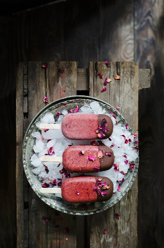 Homemade cherry and rose mangnums with a drak chocolate tip, on a dark wooden background