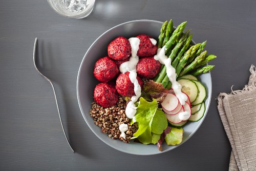 A beet falafel, quinoa, asparagus, radish, cucumber and yogurt dressing bowl