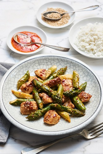 Fried green asparagus with chicken breasts in sweet and spicy sauce with rice and sesame seeds