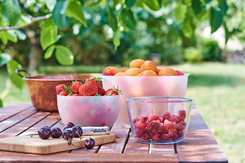 Wooden board with cherries, raspberries, apricots and strawberries in bowls on garden table