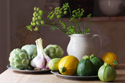 A still life with round courgettes, garlic and artichokes
