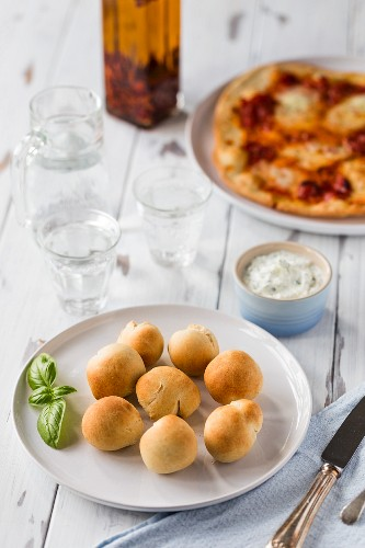 A plate of golden baked spelt doughballs with a dish of garlic herb coconut dairy free coconut butter on a white plate