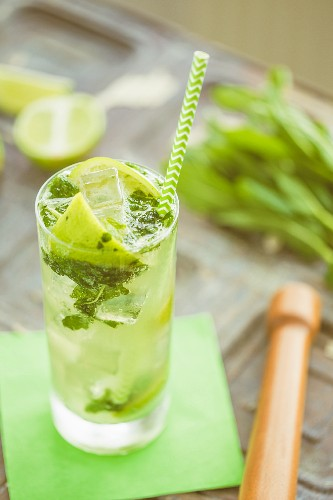Straight hiball glass with lime mint and soda water alcohol free mojito and a green stripey straw