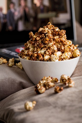 White bowl filled with cinnamon popcorn on some cushions in front of a laptop