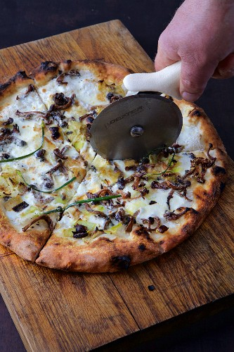 Pizza bianca with mushrooms and leek being cut with a pizza cutter