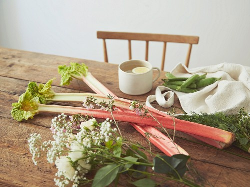 Rhubarb stems and flowers on a wooden table