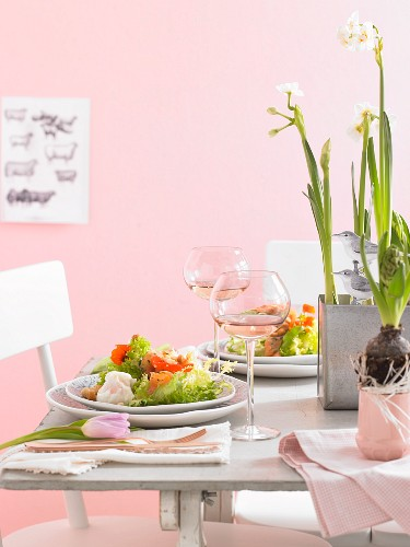A table laid with salad, wine and spring flowers for Easter