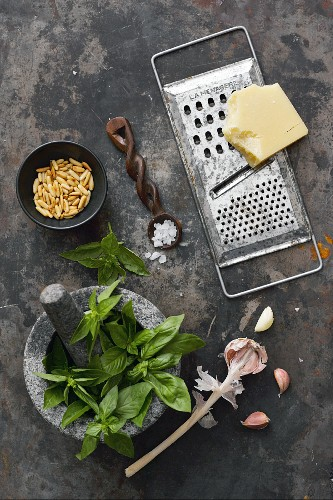 A still life with the ingredients for basil pesto