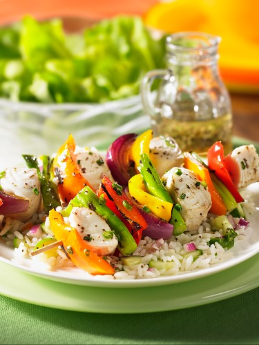 Grilled fish kebabs with peppers and onions on rice