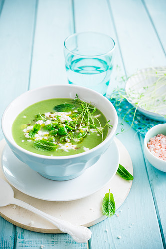 Pea and fava bean soup with beansprouts and mint leaves