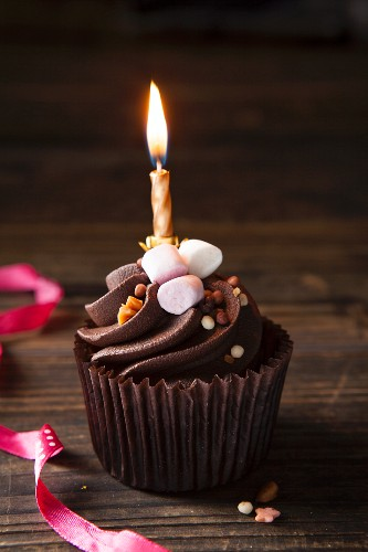 A chocolate cupcake topped with mini marshmallows, toffee sprinkles and a birthday candle
