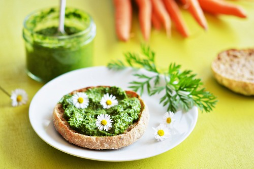 Carrot top pesto spread on bread, decorated with daisies