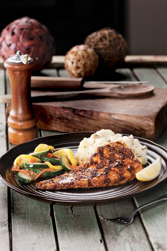 Grilled fish with rice and mixed vegetable shot on wood table with large peppermill