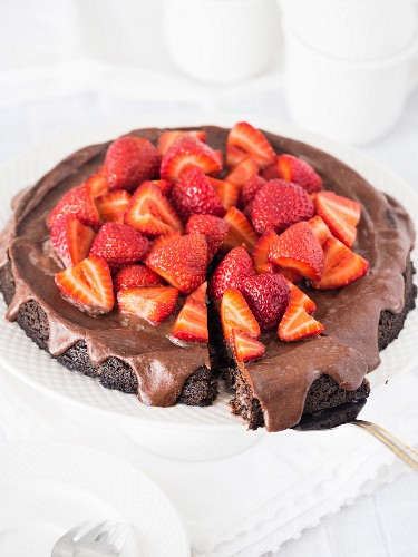 Vegan flourless (gluten free) chocolate tart with poppy seeds and chocolate frosting, served with strawberries