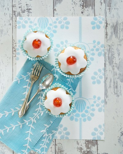 Cupcakes decorated with icing and glace cherries (top view)