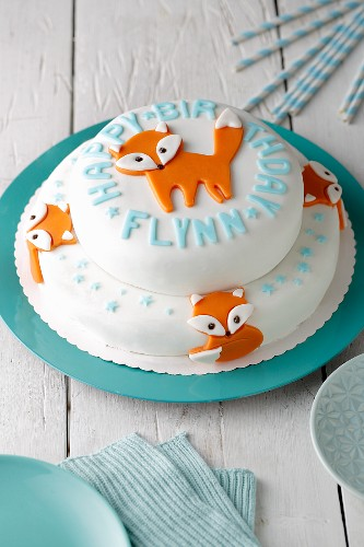 A two tier birthday cake covered with white fondant and orange foxes