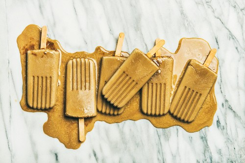 Summer healthy vegan frozen dessert: Flatlay of melting coffee latte popsicles over grey marble background
