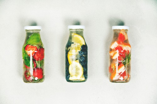 Detox fruit infused flavored water. Refreshing summer homemade cocktail on grey background
