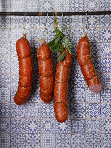 Susländer pork sausages hanging on hooks in front of a tiled wall