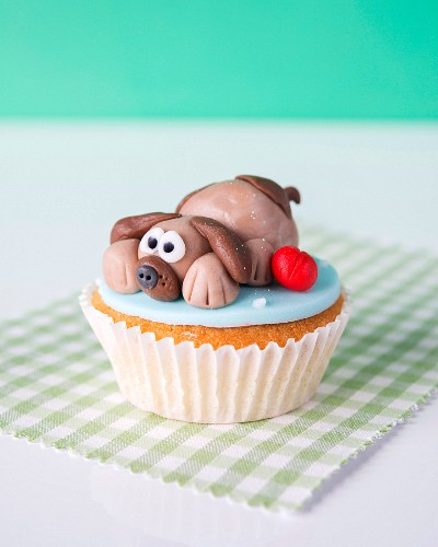 A cupcake with a marzipan dog on the top