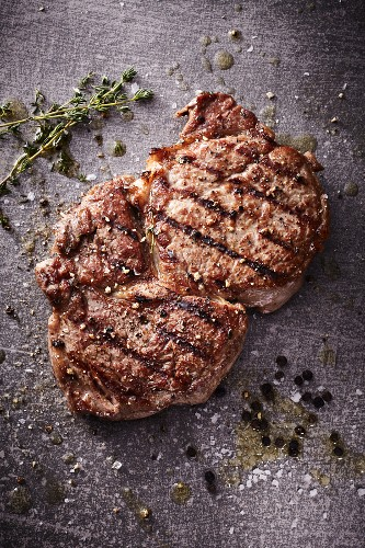 A grilled rib-eye steak with thyme, salt and pepper