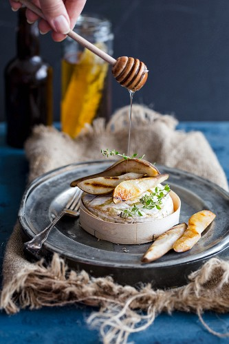 Honey being drizzled over baked Camembert and honey-glazed pear