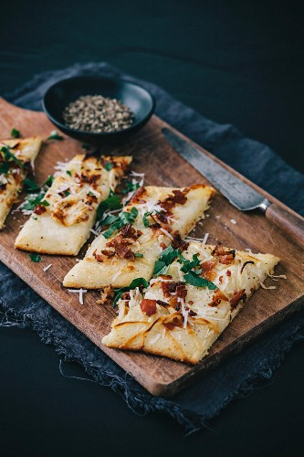 A sliced tarte flambée with bacon and cheese on a wooden board